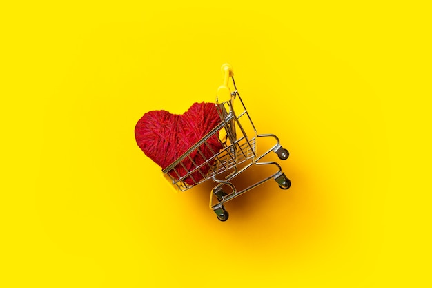 Shopping cart with a red handmade heart flies on a bright yellow background.