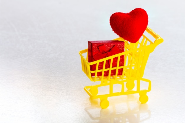 Shopping cart with red present box and confetti red hearts on a gray background copy space