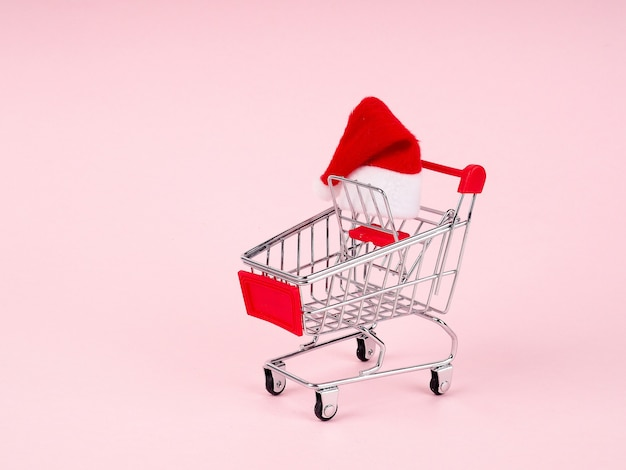 Shopping cart with santa hat on pink