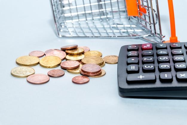 コインが散らばったショッピングカートと電卓。コンセプトローン、投資、年金、お金の節約、資金調達、担保、負債、住宅ローン、金融危機または上昇
