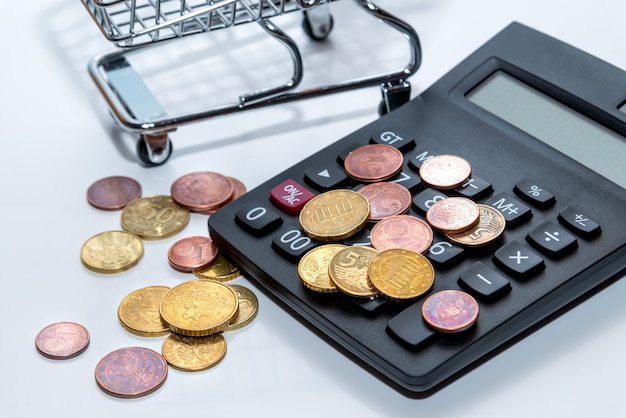Shopping cart  with scattered coins and a calculator. concept loan, investment, pension, saving money, financing, collateral, debt, mortgage