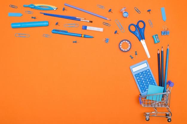 オレンジ色の背景に学用品のショッピングカート