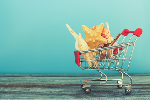 Shopping cart with seashells on blue background