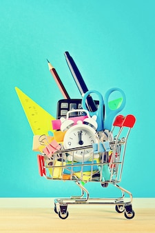 Shopping cart with stationery objects. office, school supplies.