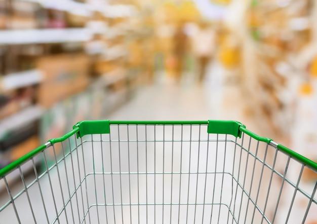 배경에 모호한 선반에 제품이있는 슈퍼마켓 통로가있는 쇼핑 카트