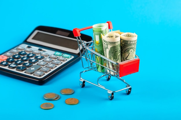 電卓にユーロとドルが入ったショッピングカート。