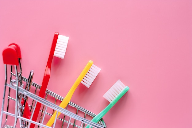 Shopping cart with toothbrush on pink background