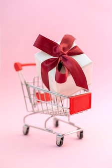 Shopping cart with white gift box and red bow vertical orientation holiday shopping concept