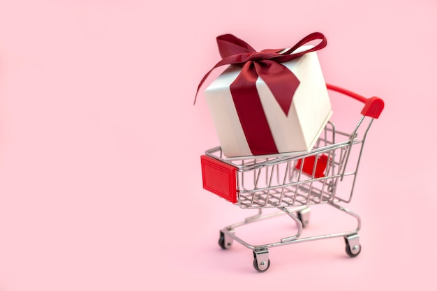 Shopping cart with white gift box with red bow inside holiday shopping concept