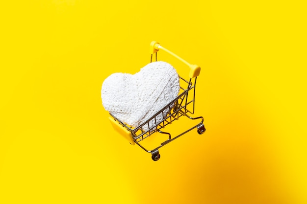 Shopping cart with a white handmade heart flies on a bright yellow background.
