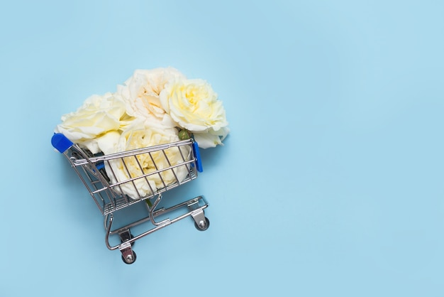 Shopping cart with white roses on blue background with copy space