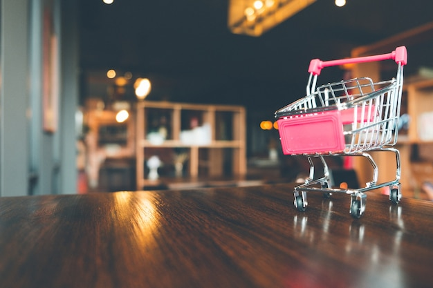 Shopping cart on wooden table in shop, online shopping and ecommerce concept.