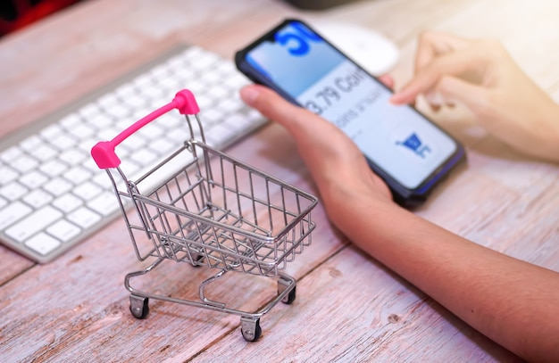 Shopping cart on wooden table behind a woman using a blurry smartphone online shopping
