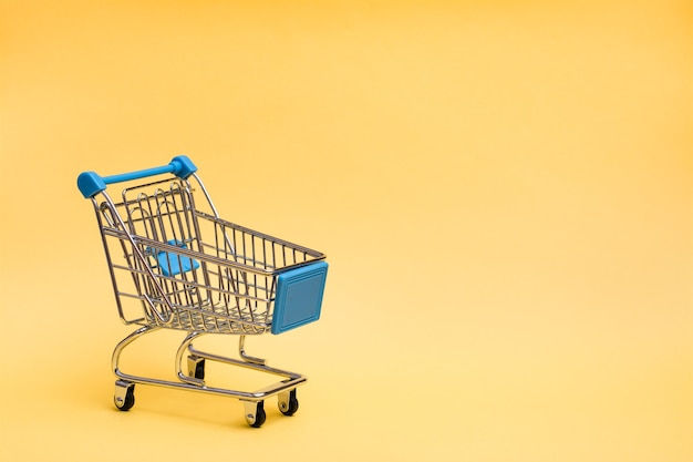Shopping cart on a yellow background. black friday gift sales. copy space