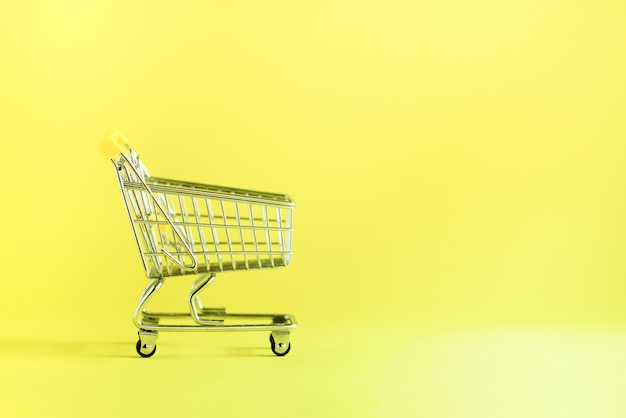 Shopping cart on yellow background. shop trolley at supermarket. sale, discount, shopaholism concept. consumer society trend
