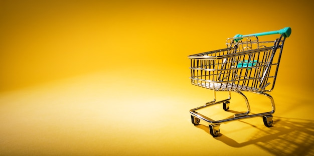 Shopping cart on yellow background in spotlight