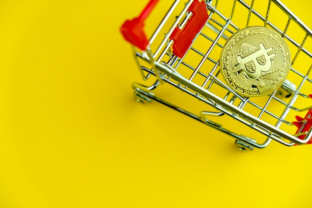 Shopping cart on yellow with bitcoin insidel. symbol of e-commerce