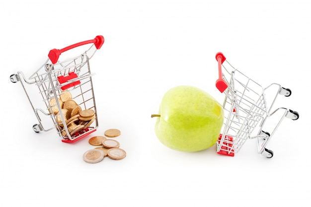 Shopping carts with euro coins falling from it on white background and green apple. sale, abundance, harvest, supermarket shopping, sale and cash back theme.