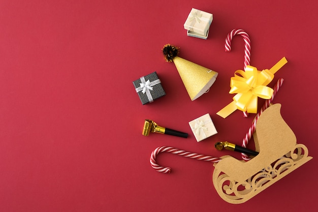 Shopping composition with xmas gifts, ribbon, candy in christmas sleigh over red banner