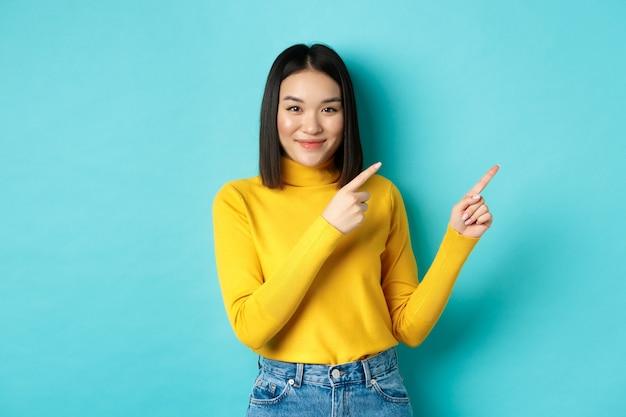쇼핑 개념. 완벽 한 피부를 가진 매력적인 젊은 아시아 여자, 유행 노란색 스웨터와 청바지를 입고, 오른쪽 손가락을 가리키고 웃 고, 광고 게재.