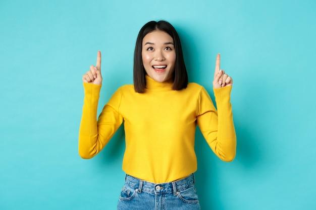 쇼핑 개념. 파란색 위에 서 행복 한 미소로 승진보고 로고에서 손가락을 가리키는 노란색 스웨터에 아름 다운 아시아 여자.