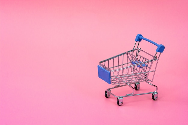 Shopping concept : blue shopping cart on pink . online shopping consumers can shop from home and delivery service. with copy space