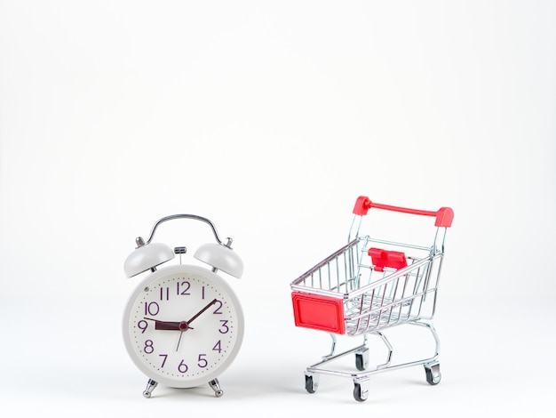 Shopping concept of cart and analog clock on the white background