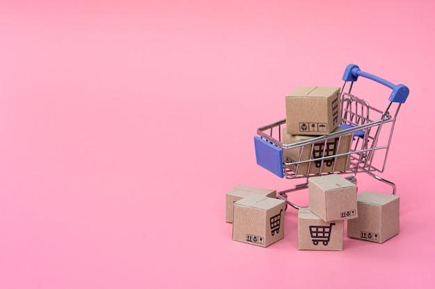 Концепция покупок: коробки или бумажные коробки в голубой тележке на розовом фоне. покупатели в интернете могут делать покупки из дома и через службу доставки. с копией пространства