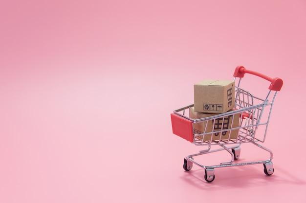 Концепция покупок: картонные коробки или бумажные коробки в голубой тележке на розовом фоне. покупатели в интернете могут делать покупки из дома и через службу доставки. с копией пространства