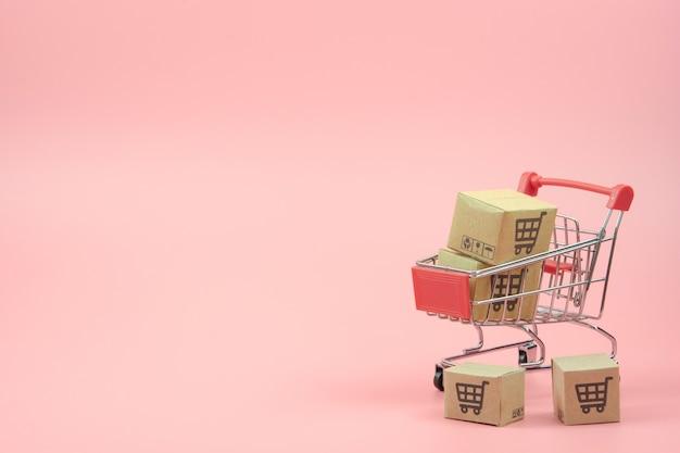 ショッピングの概念-ピンクの背景に赤いショッピングカートのカートンまたは紙箱。オンラインショッピングの消費者は、自宅や配送サービスから買い物をすることができます。コピースペース付き