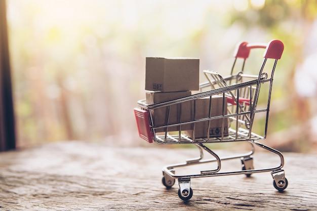 쇼핑 개념-판지 또는 갈색 나무 테이블에 장바구니에 종이 상자. 온라인 쇼핑 소비자는 가정 및 배달 서비스에서 쇼핑 할 수 있습니다. 복사 공간