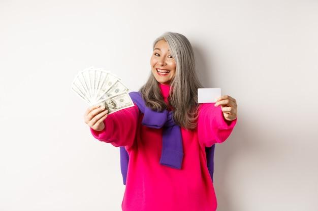 ショッピングのコンセプト。現金とプラスチックのクレジットカードを示して、カメラに微笑んで、白い背景の上に立っている陽気なアジアの年配の女性