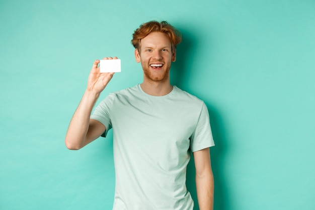 Shopping concept. cheerful young man in t-shirt showing plastic credit card and smiling, standing over mint background.