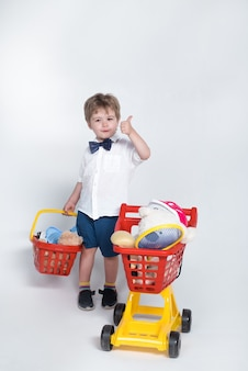 Shopping concept child with shopping basket and shopping cart giving thumb up toddler boy with child