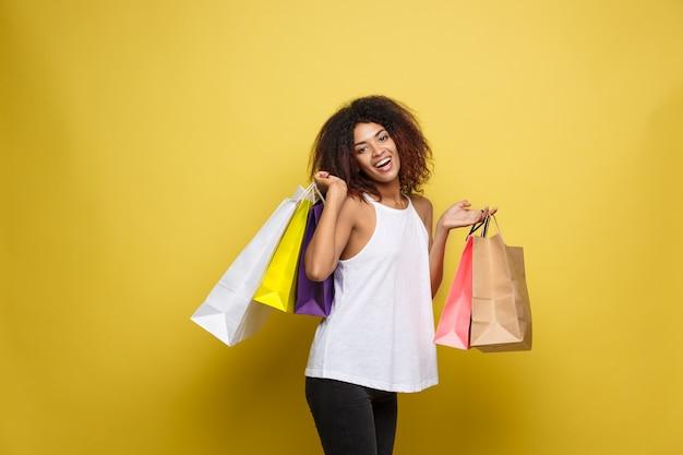Концепция покупки - закрыть портрет молодой привлекательной привлекательной африканской женщины улыбается и радостно с красочной сумкой. желтая пастель стены фона. копирование пространства.