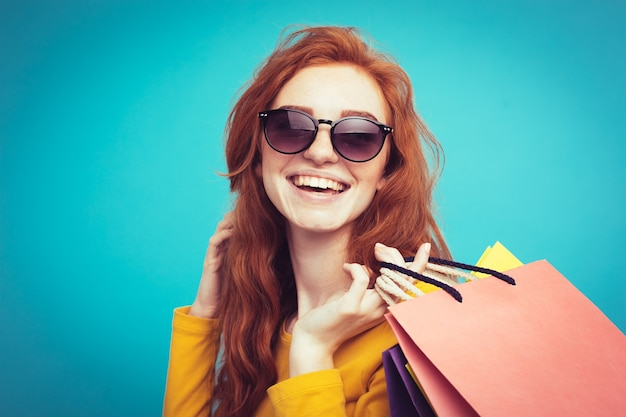 Shopping concept - close up portrait young beautiful attractive redhair girl smiling looking at camera with shopping bag. blue pastel background. copy space.