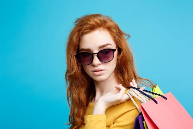 ショッピングのコンセプトは、肖像画の若い美しい魅力的な赤毛の女の子がショッピングバッグの青いパステルカラーの壁のコピースペースで笑ってクローズアップ