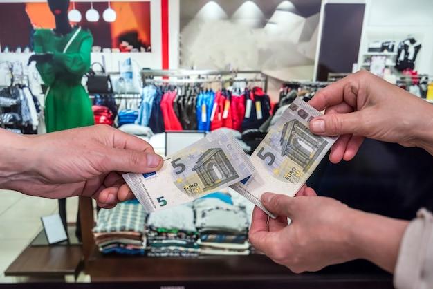 쇼핑 개념. 고객은 매장에서 유로를 지불합니다. 유로 지폐