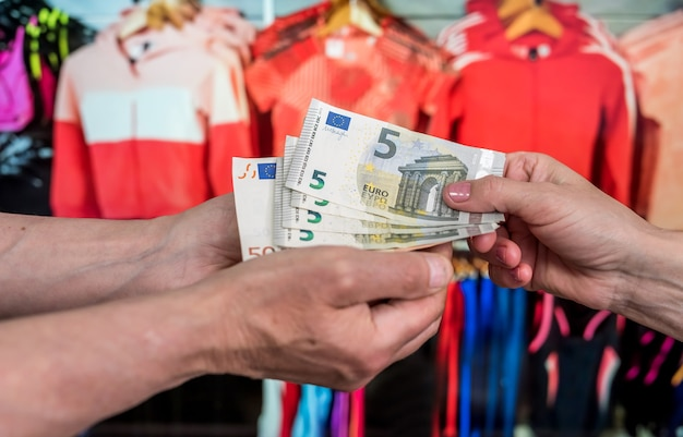 ショッピングのコンセプト。顧客は店頭でユーロを支払います。ユーロ紙幣