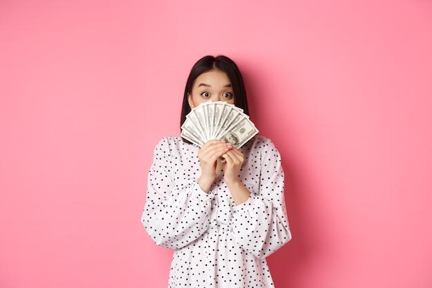 Concetto di shopping carino donna asiatica che nasconde la faccia dietro i dollari di denaro che sbirciano la telecamera in piedi sopra p...