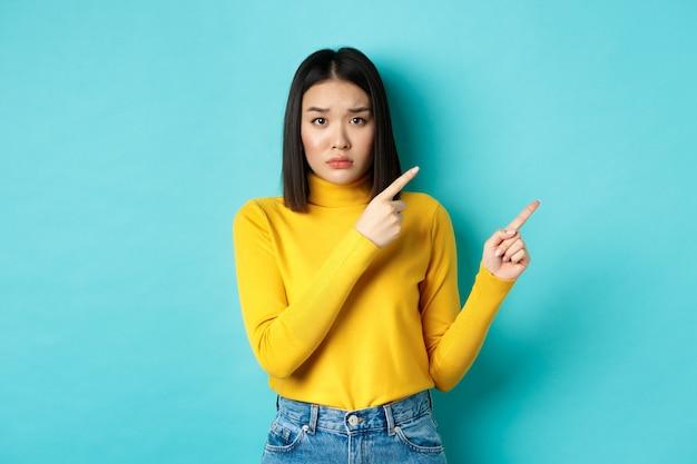 ショッピングのコンセプト。暗い顔をして、これを買うように頼み、右上隅に指を向け、カメラ、青い背景を悲しそうに見つめている失望した韓国の女の子