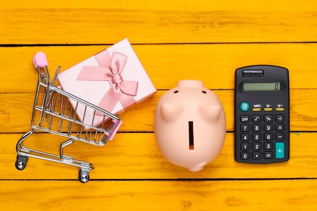 Торговая концепция, экономика. копилка с тележкой супермаркета и калькулятором, подарочной коробкой на желтой деревянной поверхности. вид сверху