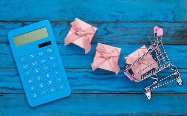 Торговая концепция, экономика. тележка супермаркета с подарочными коробками и калькулятором на голубой деревянной поверхности. вид сверху