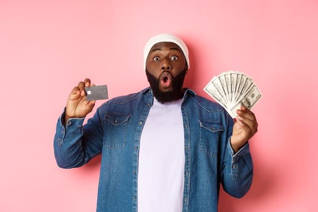Concetto di acquisto. eccitato uomo afroamericano che mostra carta di credito e dollari, ha ottenuto un deposito o un prestito di denaro, in piedi su sfondo rosa