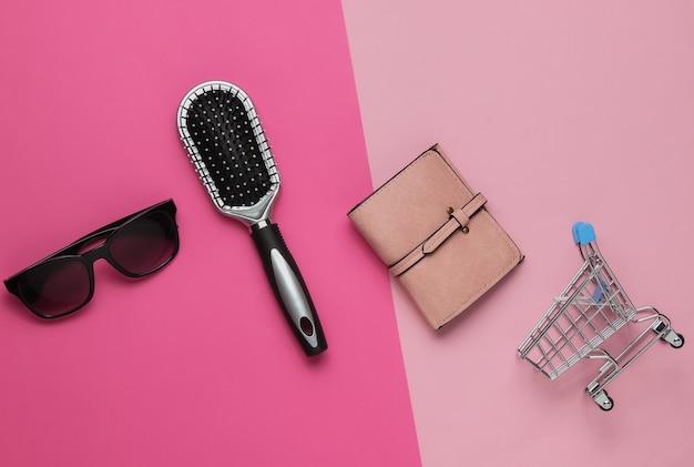 쇼핑 개념 유행 여성 액세서리 가죽 지갑 빗 선글라스 분홍색 배경에 미니 쇼핑 트롤리