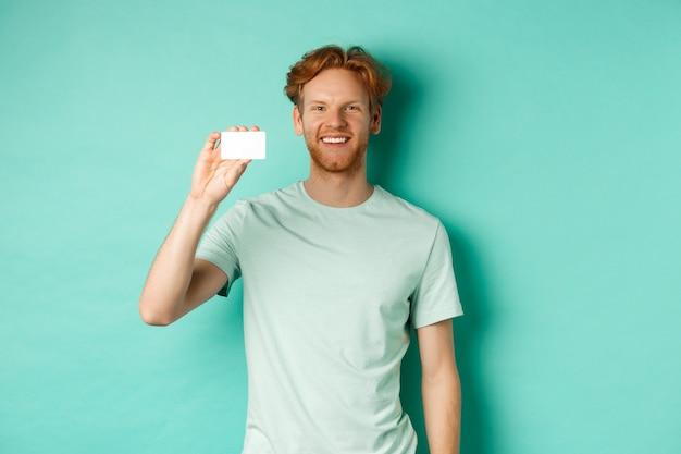 ショッピングのコンセプト。ターコイズブルーの背景の上に立って、プラスチックのクレジットカードと笑顔を示すtシャツのハンサムな赤毛の男。