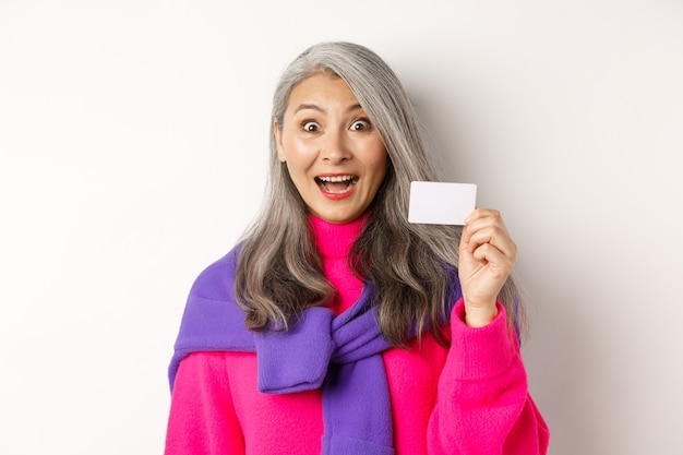 ショッピングのコンセプト。感動し、白い背景の上に立って、彼女の銀行のプラスチックのクレジットカードを示している幸せなアジアの古いアルディ。