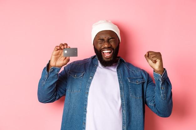 Concetto di acquisto. felice uomo nero che si rallegra, urla di gioia e mostra la carta di credito, in piedi su sfondo rosa.