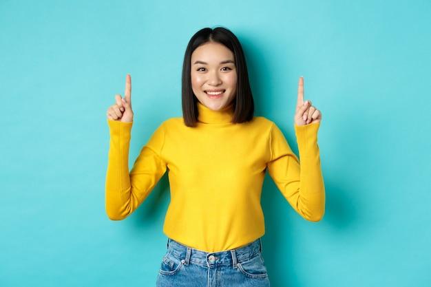 쇼핑 개념. 노란색 스웨터에 아름 다운 베트남 여자, 광고 게재, 웃 고 손가락을 가리키는 파란색 위에 서있는 이미지.