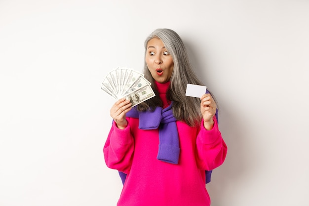Shopping concept. lucky asian senior woman looking amazed at money and showing plastic credit card, standing over white background.